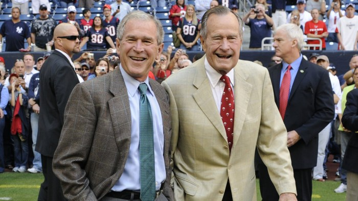 FILE - This Oct. 25, 2009 file photo shows former Presidents George H. W. Bush, right, and George W. Bush before the Houston Texans NFL football game ...