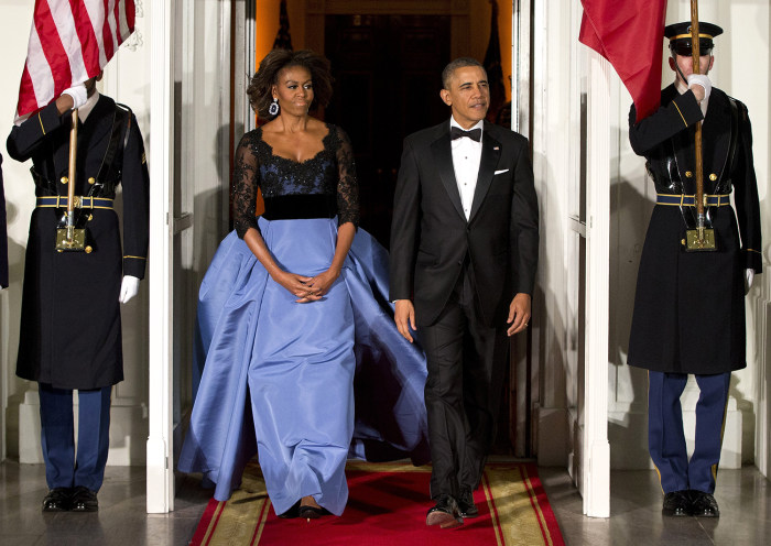 First lady Michelle Obama, left, and President Barack Obama wait for the arrival of French President François Hollande for a State Dinner at the Nort...