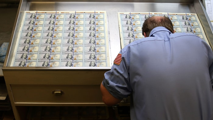A worker inspects newly redesigned $100 notes during the printing process at the Bureau of Engraving and Printing last year.