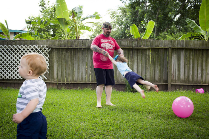 Image: Lance Stewart swings around his daughter Brooklyn, 3, while his son Connor, 1, wanders by at their home in League City, Texas.