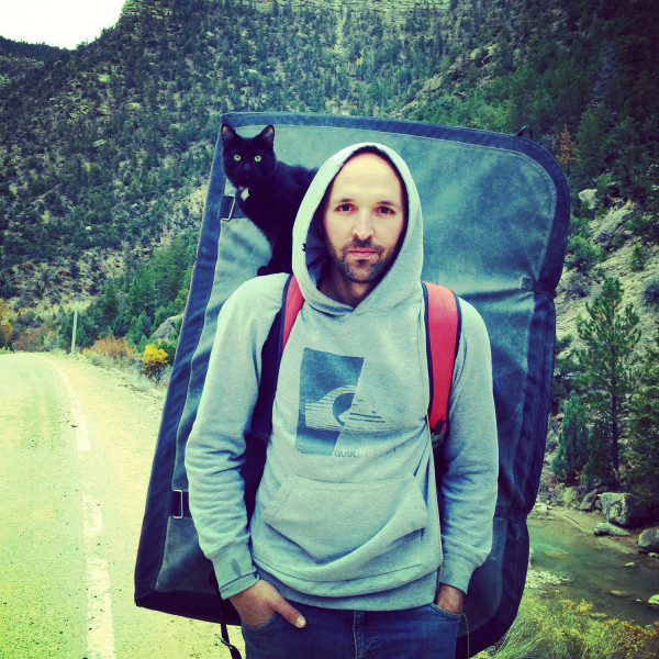 Millie the cat's first climbing adventure was a day trip to Joe's Valley for some bouldering. She's perched atop Craig Armstrong, who is wearing a bouldering pad on his back.
