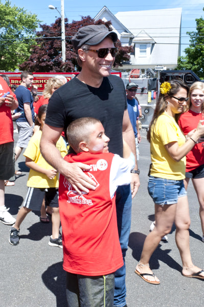 Mario Carpino gives his new friend, Jon Bon Jovi, a big hug while walking around Carpino's cancer fundraiser.