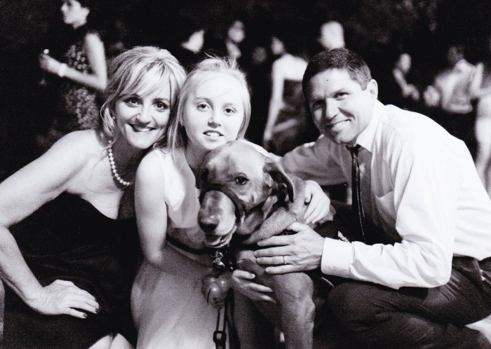 Rachel Benke and her family, including her guide dog Taxi, pose for a photo at a wedding.