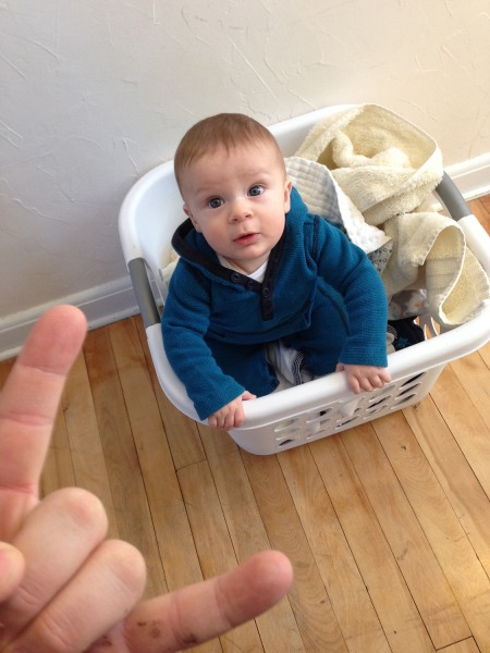 Brian Reda's son Livingston looks up at his dad from a laundry basket. Rock on!