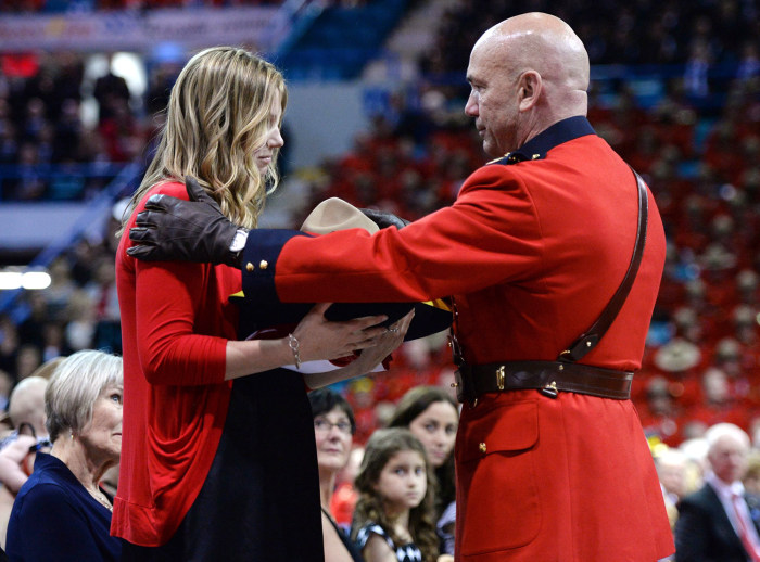 Royal Canadian Mounted Police Commissioner Bob Paulson, right, presents Constable Dave Ross's widow Rachael with the slain RCMP officer's Stetson duri...