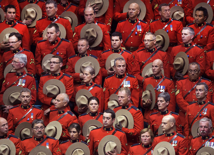 RCMP officers stand in silence during the regimental funeral of three slain officers at the Moncton Coliseum on Tuesday, June 10, 2014, in Moncton, Ne...