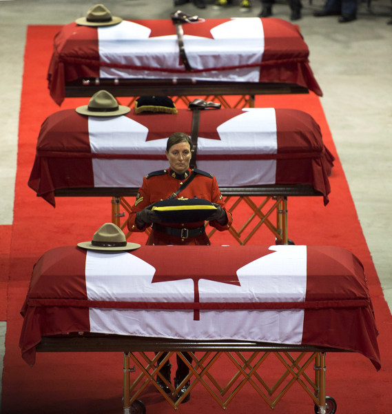The caskets of the three RCMP officers who were killed in the line of duty are draped witth the Canadian flag at the regimental funeral at the Moncton...