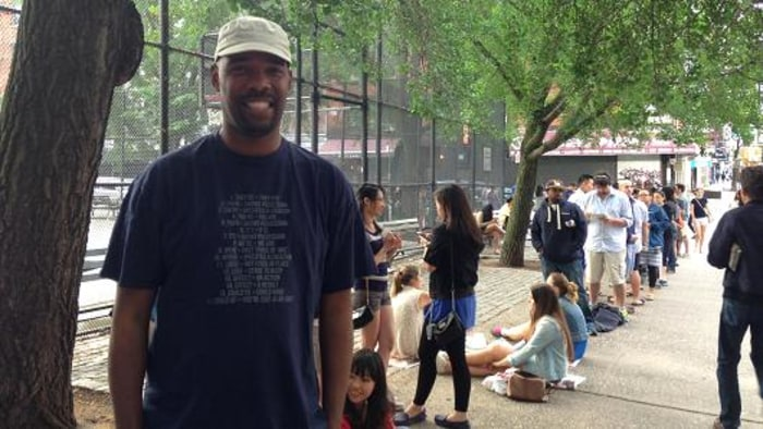 Robert Samuel, founder of Same Ole Line Dudes, waits in a line for Cronuts at Dominique Ansel Bakery in New York.