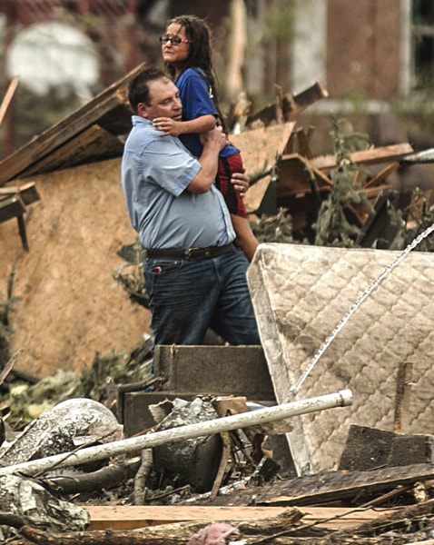 A man holds a girl after she was pulled from the basement of her destroyed home in Pilger, Neb., Monday, June 16, 2014. A hospital spokeswoman says at...
