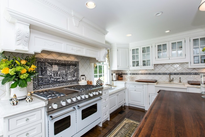 The home features an all-white kitchen, eight bedrooms and eight fireplaces.