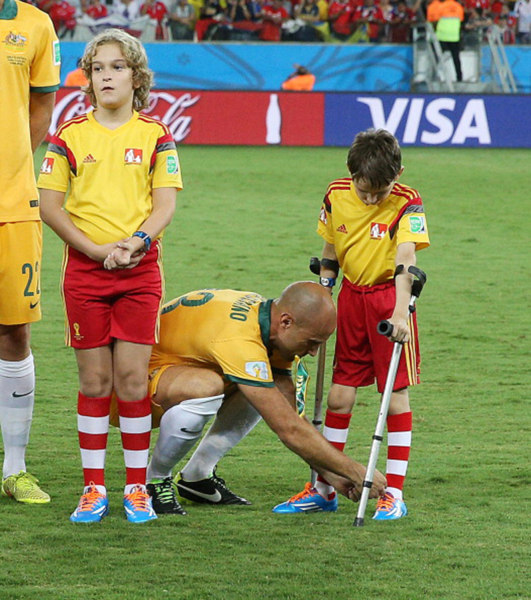 Mark Bresciano, a midfielder for Australia, bends down to help tie the shoe laces of a boy on crutches ahead of a World Cup match against Chile in a touching photo that has warmed hearts across the world.