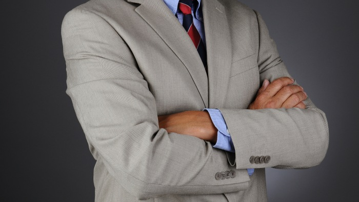 Closeup of a businessman standing with his arms crossed.