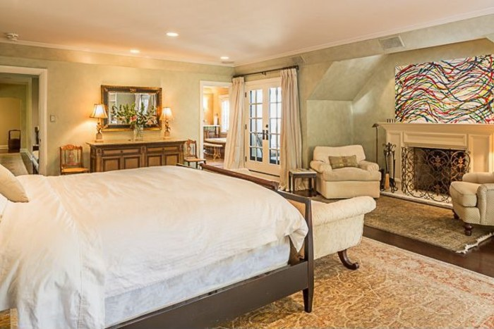 The master bedroom includes a balcony overlooking gardens and the pool.
