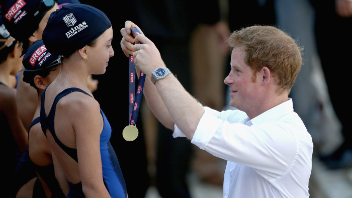 Prince Harry presents medals to young swimmers during a visit to Minas Tênis Clube on June 24 in Belo Horizonte, Brazil.