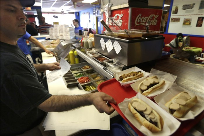An employee at Hot Doug's in Chicago prepares an order May 7, 2014, at the gourmet hot dog diner.