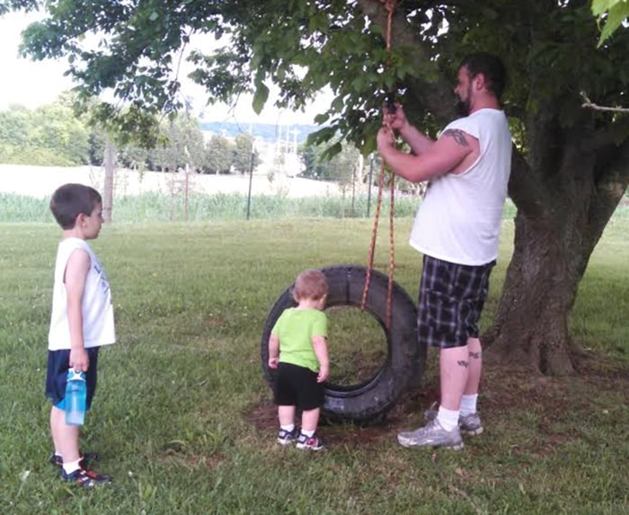 Danny Rogers building a tire swing for sons Timothy and William.