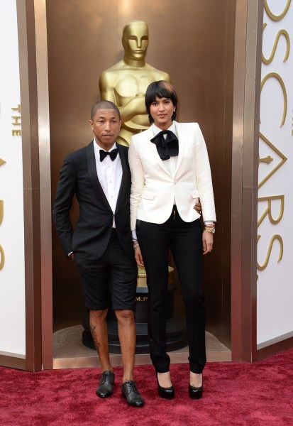 Pharrell Williams (L) and Helen Lasichanh arrive on the red carpet for the 86th Academy Awards on March 2nd, 2014 in Hollywood, California. AFP PHOTO ...