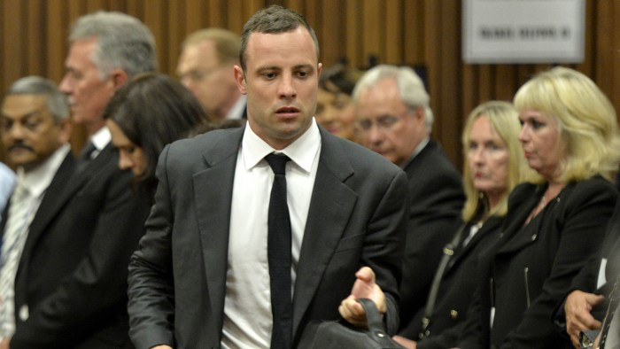South African Paralympian star Oscar Pistorius (C), accused of murdering his girlfriend Reeva Steenkamp, attends the opening day of his trial, at the ...