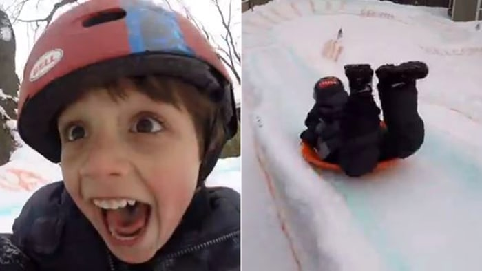 A boy rides a backyard luge.