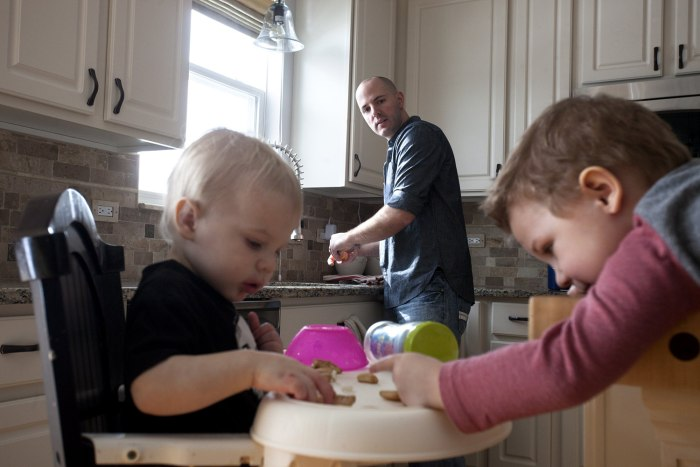 David Juip peels oranges for his two sons Ari, 1, and Jonah, 3, at their home in Wauconda, Ill. Juip has been a stay-at-home dad for two yea...