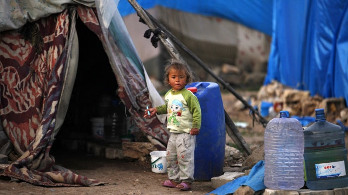 A Syrian refugee child stands outside a tent in the southeastern city of Kilis, near the Syrian-Turkish border, March 2, 2014. REUTERS/Nour Kelze (TUR...