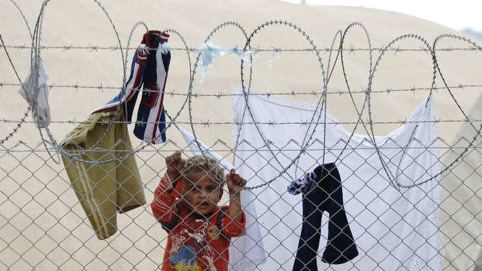 A newly arrived Syrian refugee child is seen behind the fences at Ceylanpinar refugee camp near the border town of Ceylanpinar, Sanliurfa province, No...