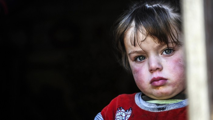 A Syrian refugee child looks out from a shelter in Hatay, Turkey, on January 20, 2014. Representatives of Syrian President Bashar al-Assad, a deeply d...