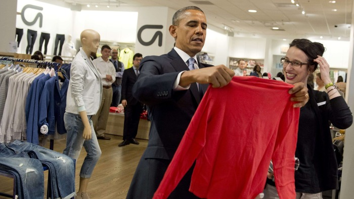 US President Barack Obama holds up a shirt as he shops for clothing for his family alongside store employee Susan Panariello (R) during a visit to a G...