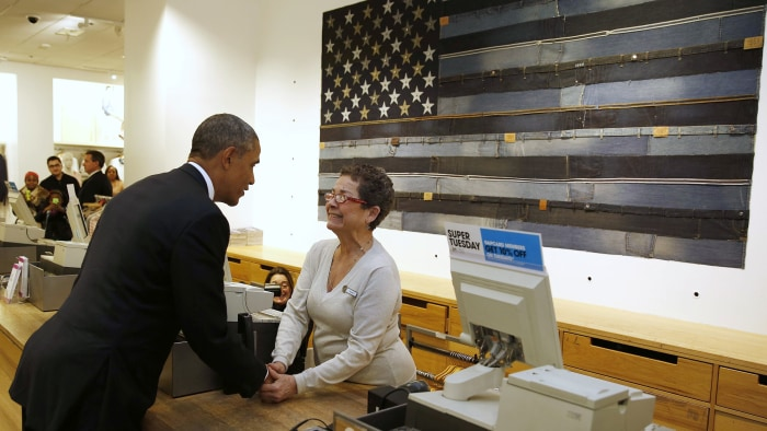 U.S. President Barack Obama shakes hands with cashier Sonia Del Gatto while he looks for gifts for his family after stopping off at the GAP in New Yor...