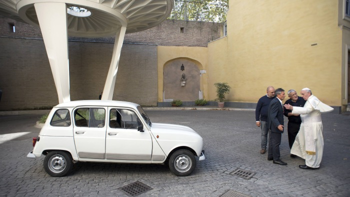 Pope Francis (R) is presented with a Renault 4 car during a private audience with Don Renzo Zocca at the Vatican in this picture taken September 7, 20...