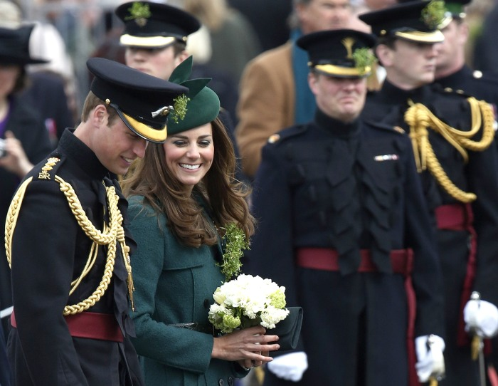 Britain's Catherine, Duchess of Cambridge (2nd L) and her husband Prince William (L) wear sprigs of shamrock during a visit to the 1st Battalion Irish...