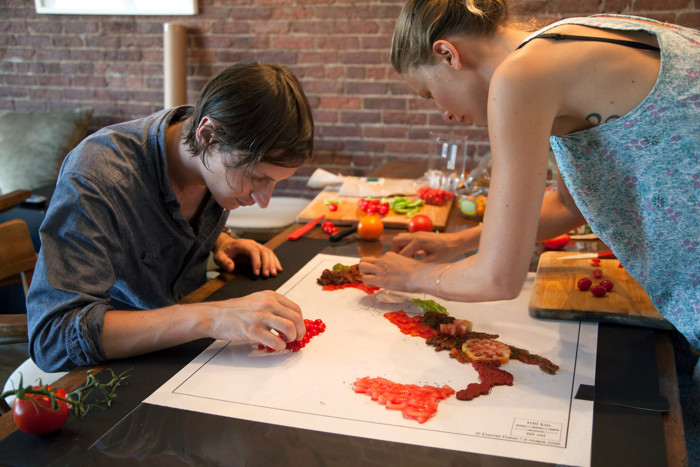 Hargreaves and Levin painstakingly arrange tomatoes around a stencil of Italy.