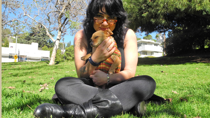 C.J. and her pet, dressed in her knitted design, share a cuddle in Los Angeles.