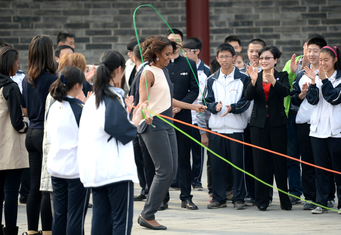 US First Lady Michelle Obama (C) skips in front of Chinese school children on the City Wall in Xian in China's central Shaanxi  province on March 24, ...