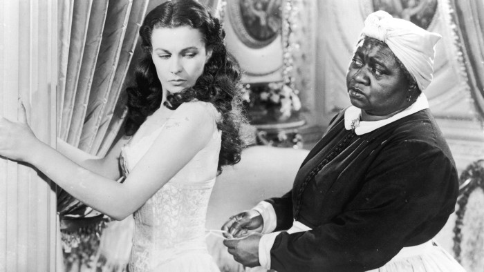 "British actor Vivien Leigh (1913-1967) holds on to a pillar as American actor Hattie McDaniel (1895-1952) tightens her corset in a still from the 1939 film ""Gone with the Wind."""