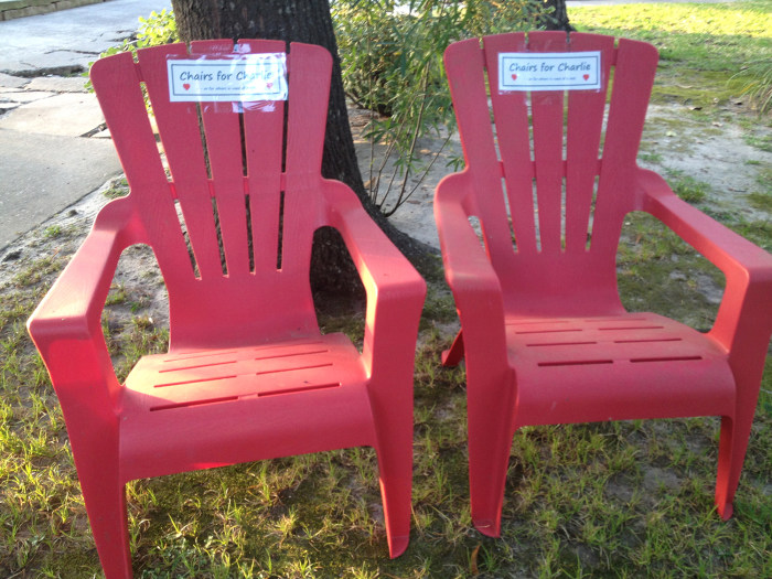 Two red Adirondack chairs with signs that say: Chairs for Charlie. They are for Charlie George, who is battling leukemia, to use as he strolls the neighborhood.