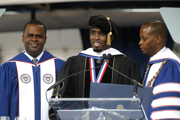 Entertainer Sean Combs (C) stands with Howard University Interim President Wayne Frederick (R) and university trustee Atlanta Mayor Kasim Reed (L) aft...