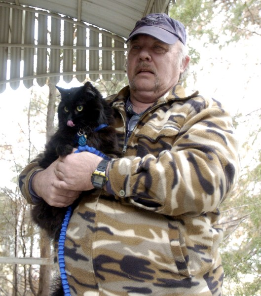 Greg Guy holds Schnautzie the cat.