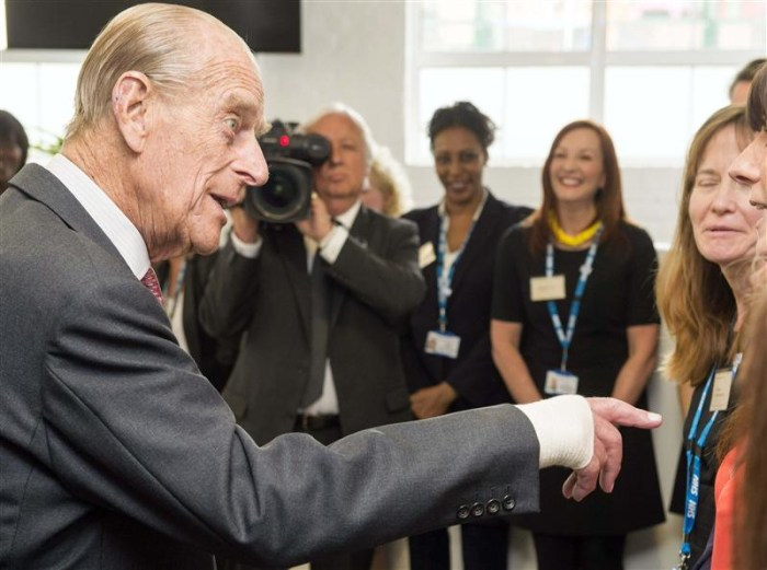 Britain's Prince Philip, left, meets members of staff during a visit to the Margaret Pyke Centre in London on Wednesday, one day after undergoing a procedure on his hand.