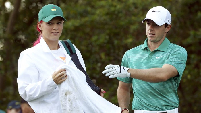 Tennis player Caroline Wozniacki of Denmark (L) works as the caddie for her boyfriend, Northern Ireland's Rory McIlroy, during the Par 3 Contest ahead...