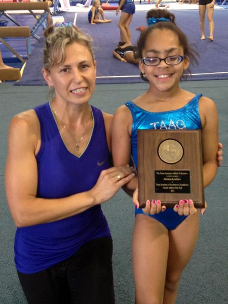Photo Adrianna and her coach holding the award