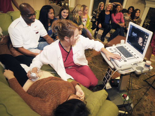 Christy Foster, co-owner of Babyface & More, does an ultrasound on expectant mother Karie Moss during a Babyface & More Ultrasound party at the home o...
