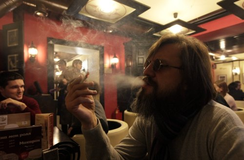 A man smokes a cigarette at a cafe in central Krasnoyarsk in Siberia January 24, 2013. Russian President Vladimir Putin has signed a law that will ban...