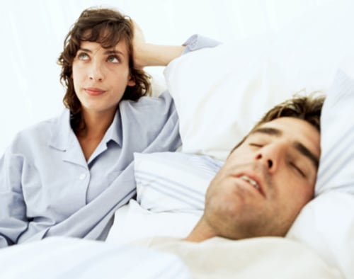 woman frustrated annoyed at man's snoring man bed couple pajamas sleep awake msnbc stock photography photo realtionship insomnia