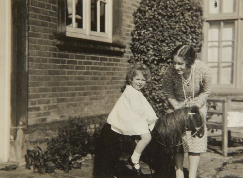 Princess Elizabeth with a toy house in front of Naseby Hall in 1928. The photo was taken by her father, King George VI when he was the Duke of York.