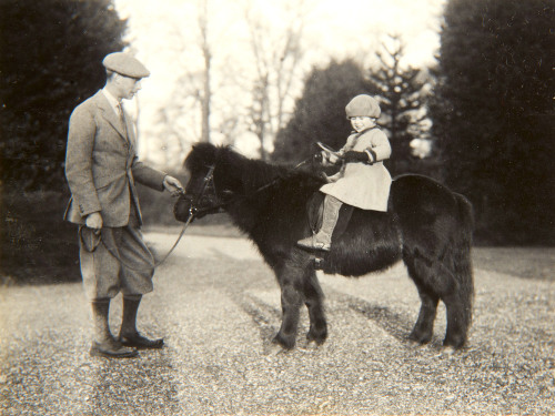 A 4-year-old Princess Elizabeth her Shetland pony named Peggy while her father King George VI, then the Duke of York stands next to her. The photo was taken by her mother Queen Elizabeth when she was the Duchess of York.