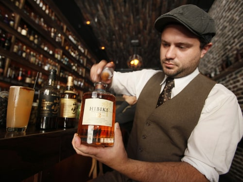 General manager Owen Westman opens a bottle of 12-year-old Hibiki Japanese whisky at the Rickhouse bar in San Francisco, Friday, Aug. 6, 2010. At left...