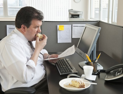 Business man eating at desk Getty Images stock overweight fat