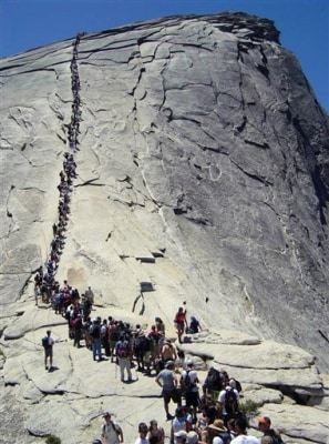 In this 2006 file photo, tourists climb Half Dome at Yosemite National Park.
