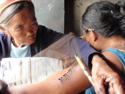 Od puts the finishing touches on Jazmine's Filipino tattoo.